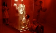 The entire installation space was painted bright red.  Three performers, painted red, interacted with viewers, while activating the space performing various tasks.  Tasks included:  writing in a red book with a red pen, knitting with red yarn while speaking Japanese, and bouncing red balls. The artists, clad entirely in white, contained themselves in a plexiglass box for the duration of the performance.